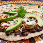 Chicken Tlayuda - Black bean, chicken tinga, onion, tomatoe, avocado, lettuce, with fresh cheese and sour cream, handmade tortilla.