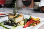 The fish of the day at La Panga is served with basil oil over mashed potatoes and grilled vegetables.